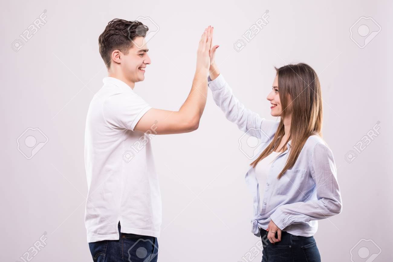 Joyful man and woman greeting each other with a high five isolated joyful man and woman greeting each other with a high five isolated on white background stock m4hsunfo