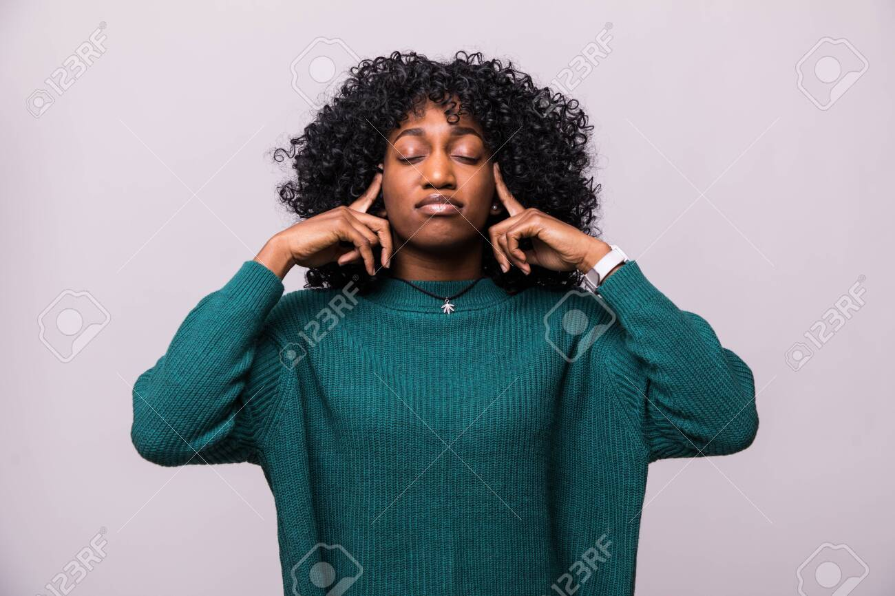 Portrait annoyed, unhappy, stressed african woman covering her ears, looking up stop making loud noise isolated on white background with copy space. - 124452087