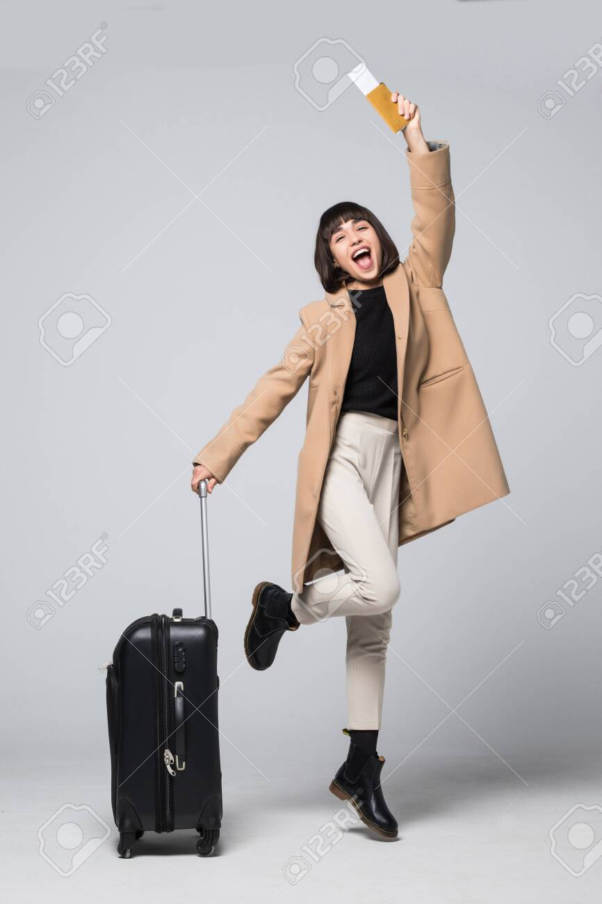 Happy young woman tourist jumping, holding suitcase and passport, flight tickets, isolated on white background - 128253059