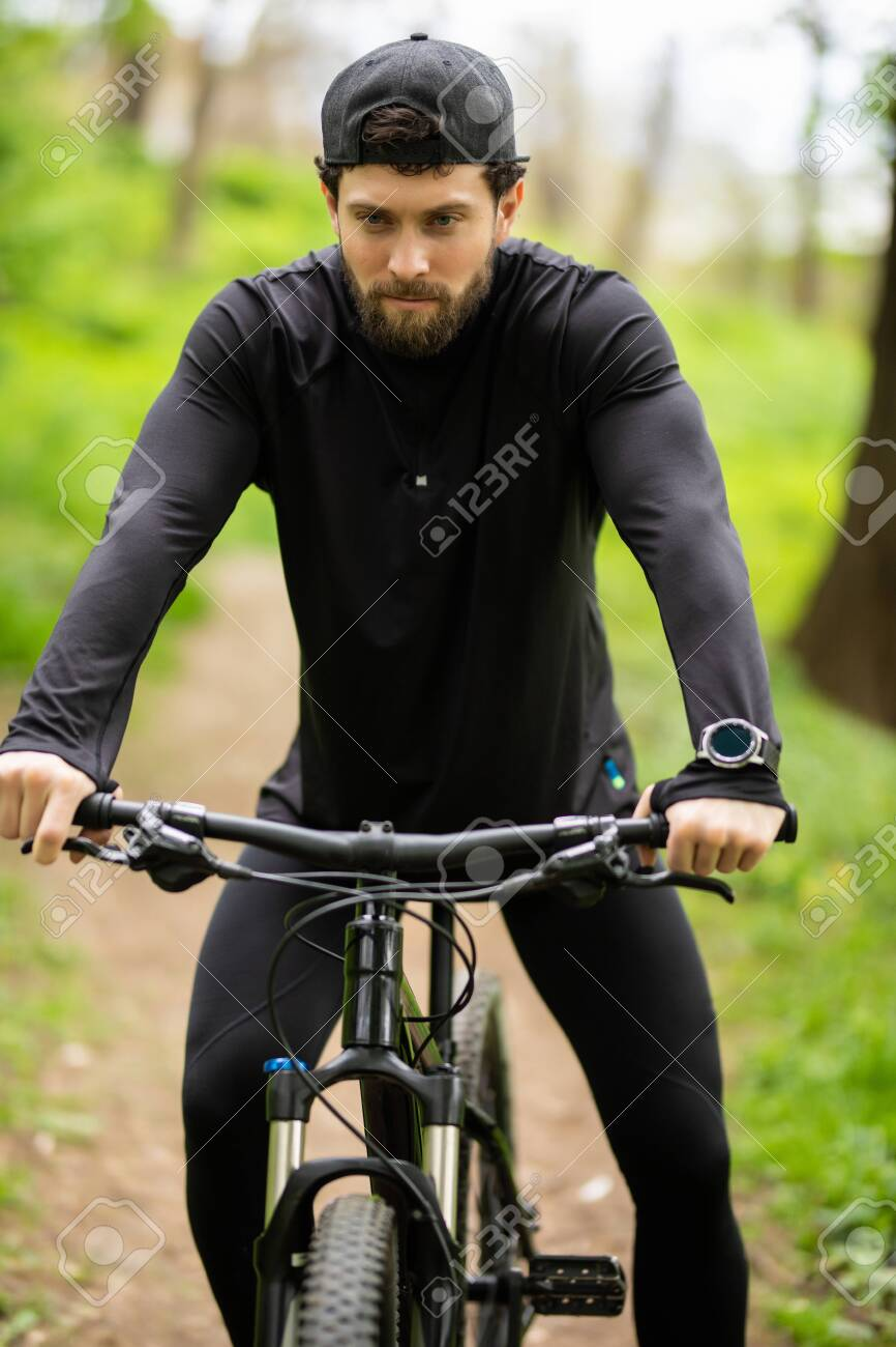 Happy Young man is riding bicycle outside. - 128916680