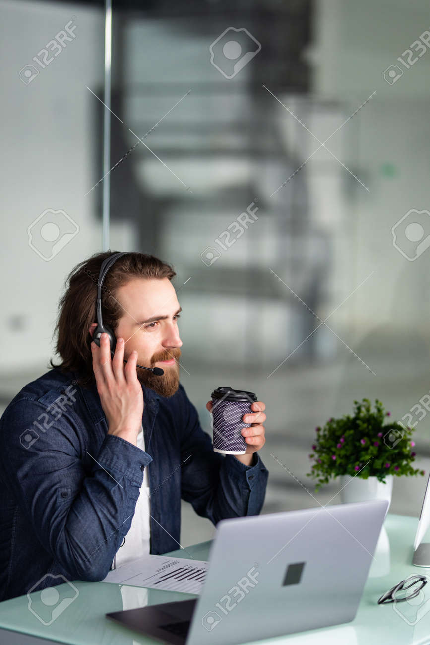 smiling young call center operator in headset working with laptop in office - 139400022