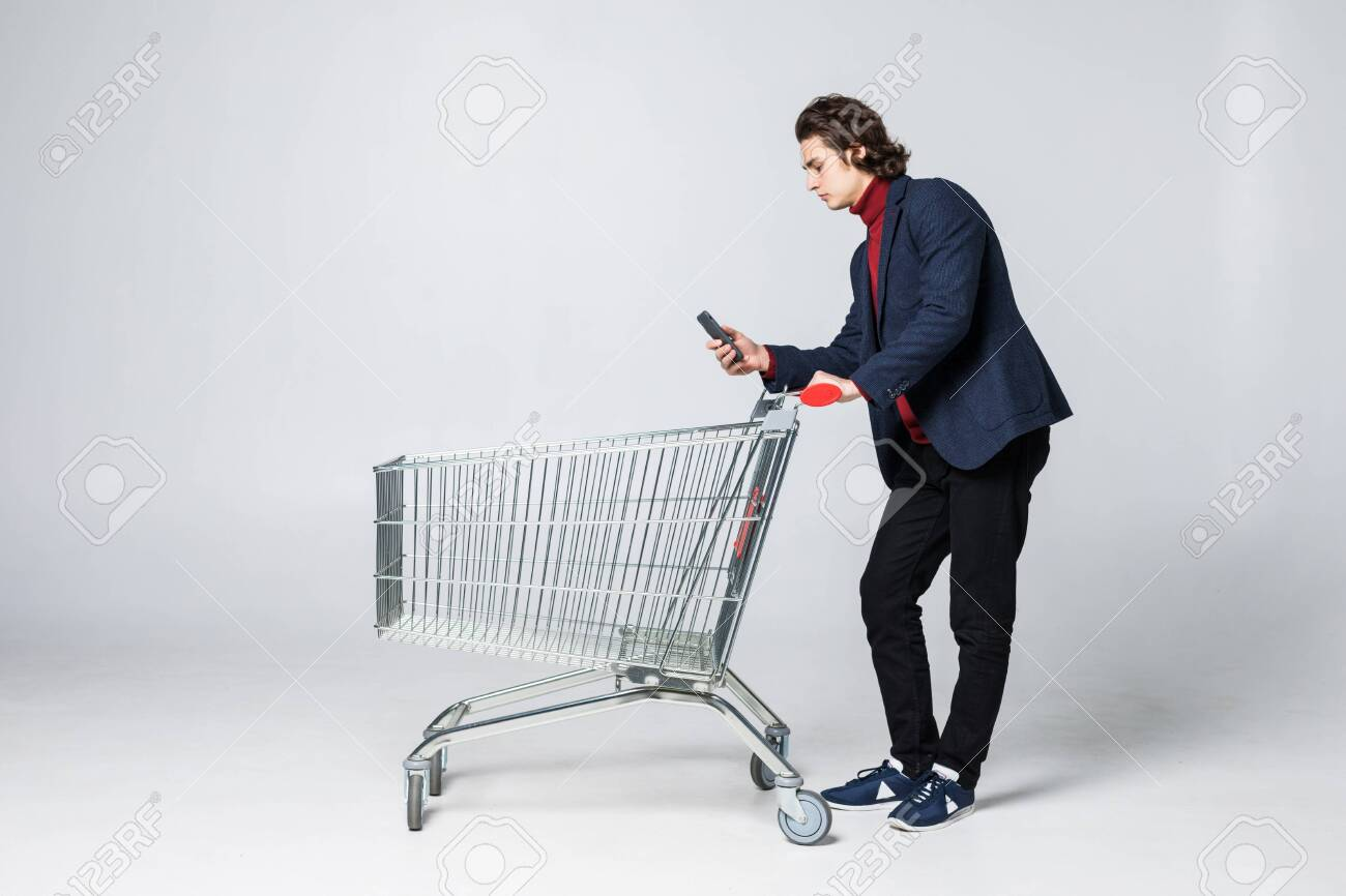 Young man holding mobile phone and shopping cart isolated on white - 141558171
