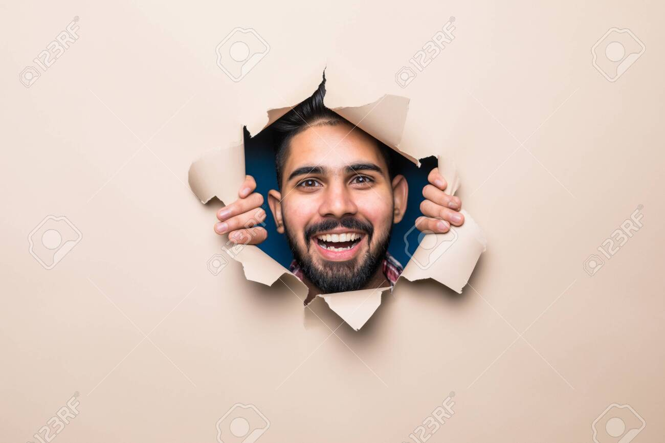Young indian bearded man smile look from beige paper hole - 142370451