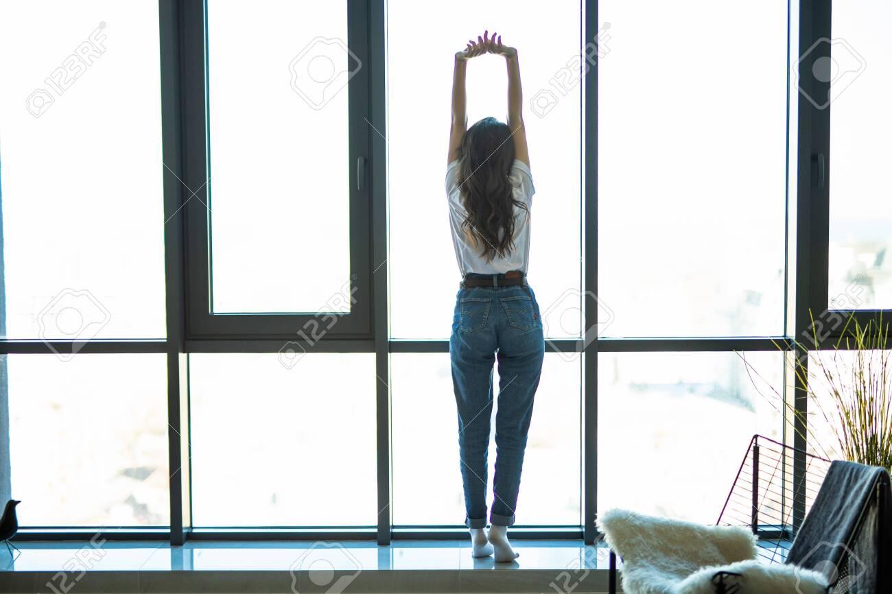 Woman near window raising hands facing the sunrise at morning - 147838594
