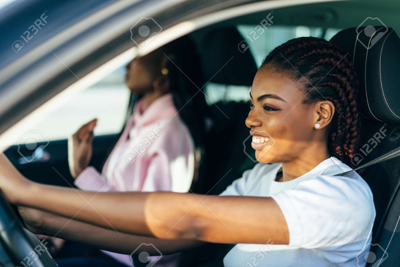 Two Female Friends On Road Trip Driving In Convertible Car - 166970266