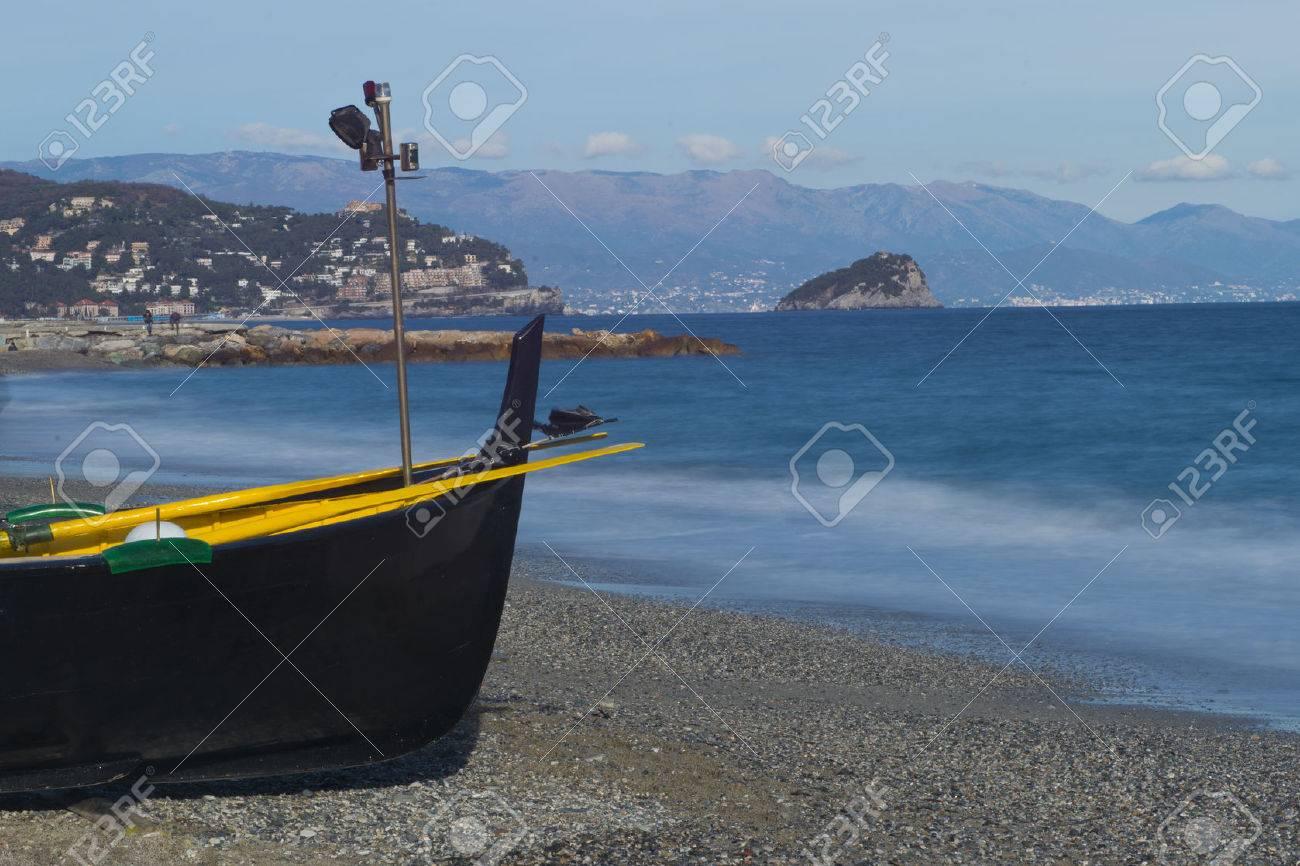 Black boat on the beach of Noli, on the Riviera ligure, Italy - 25413549