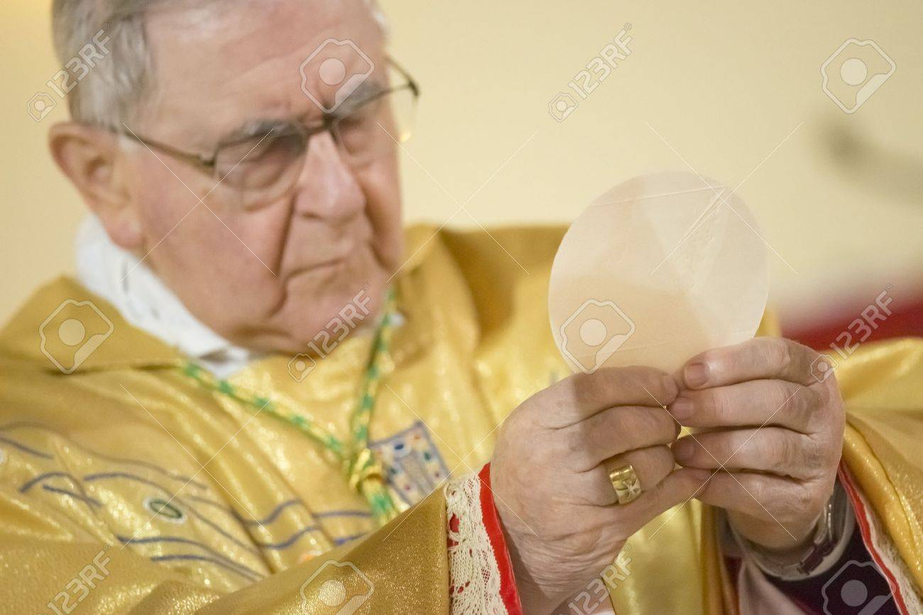 GENOA, ITALY - 14 FEBRUARY 2015 - Bishop officiating mass during the Holy Communion - 39010451