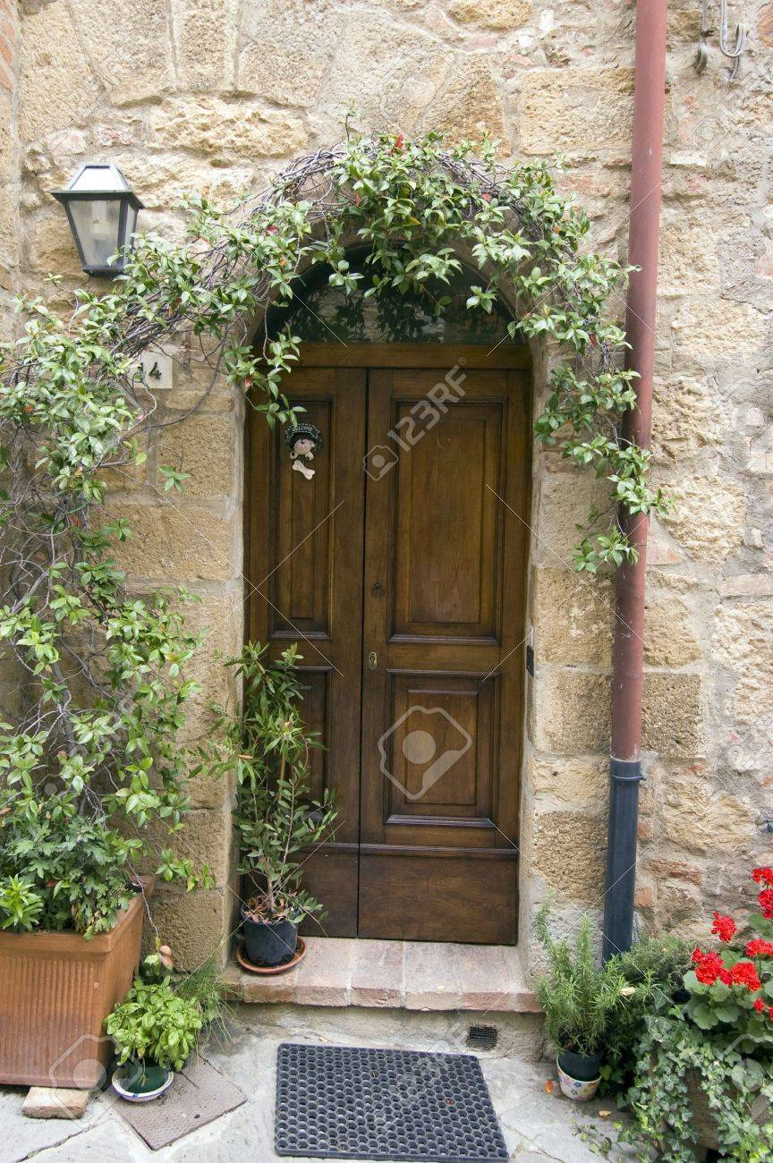 Old wooden door with potted flowers. Italian style. Tuscany Stock Photo - 4142496