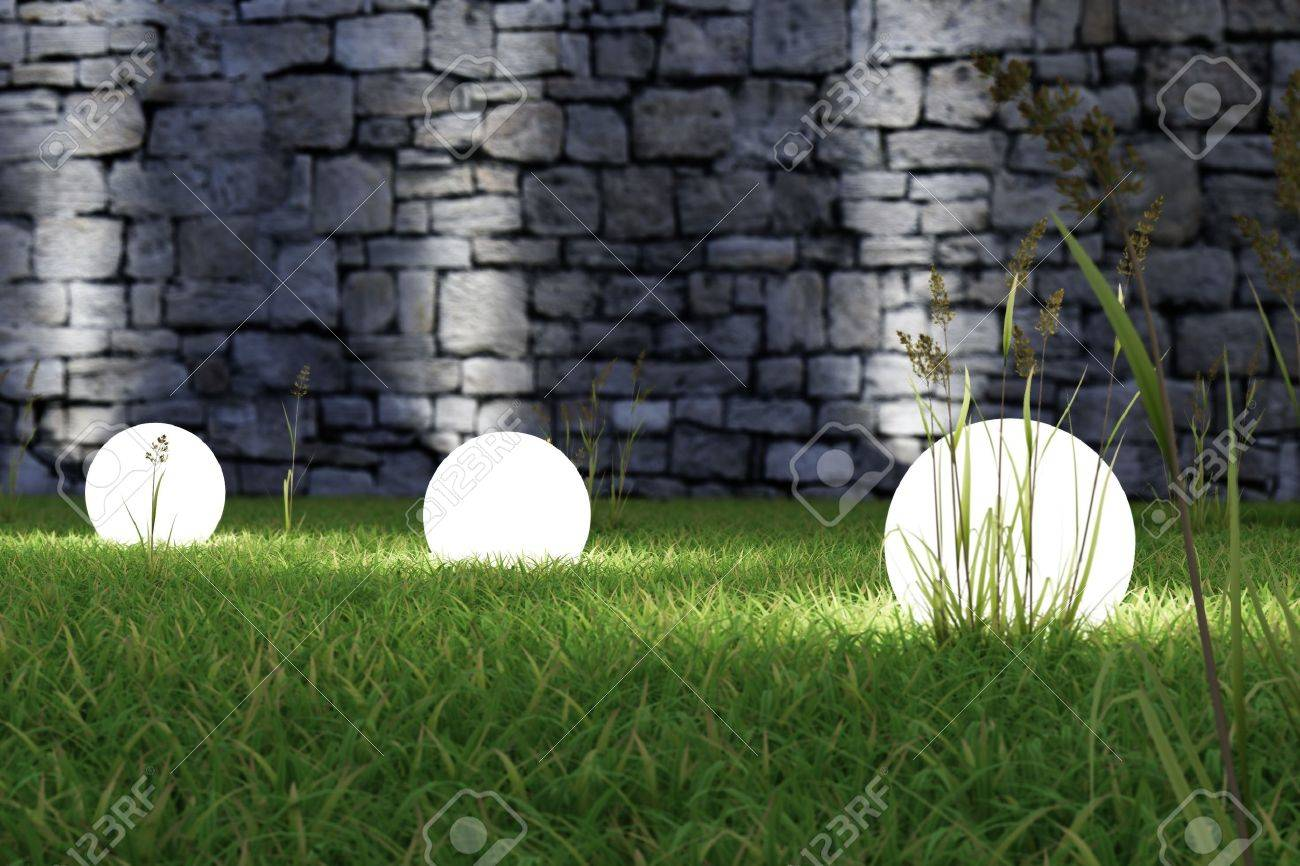 Glowing light in the grass with old wall in background - 20995354