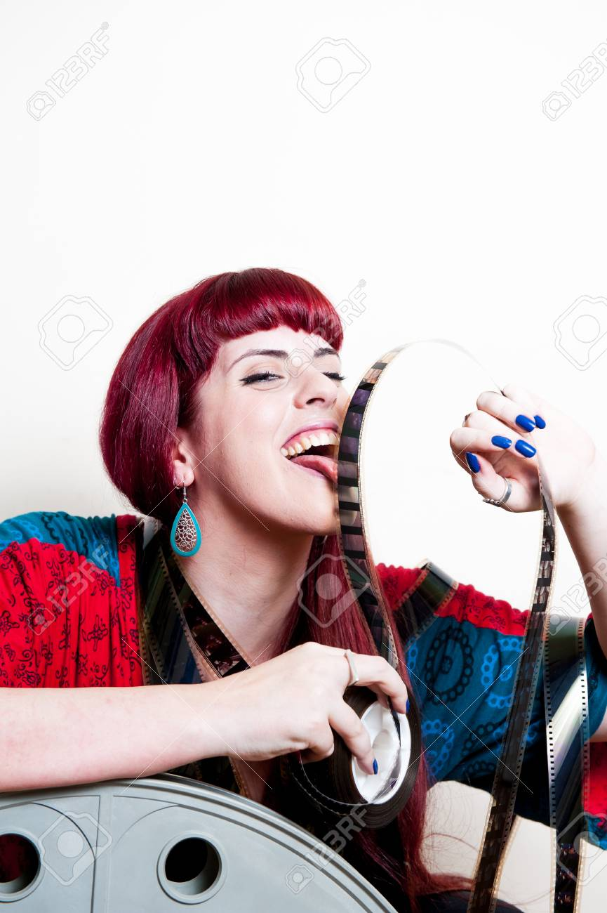 Stock Photo - Young woman smile behind big movie cinema reel licking  filmstrip on white background