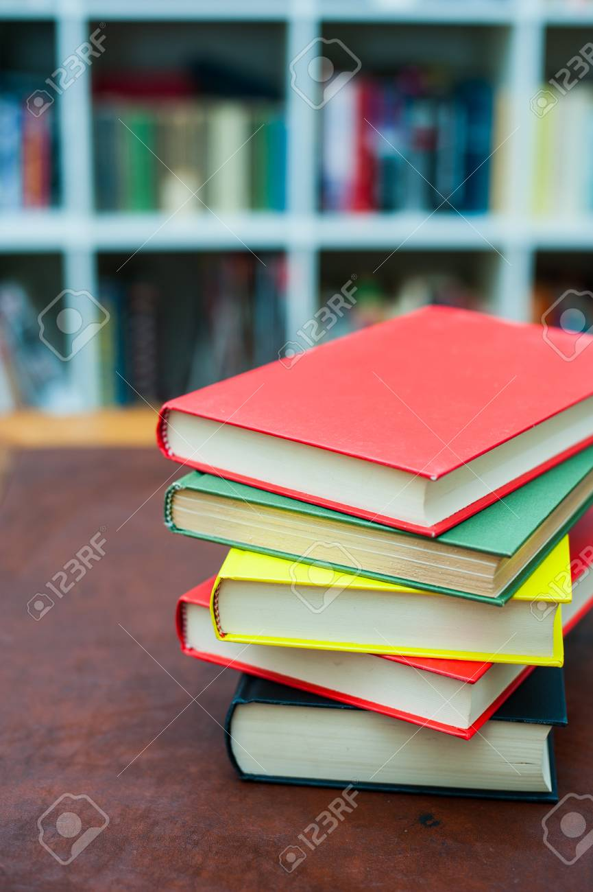 Fantastic Pile Of Colored Books On Wooden Desktop With Out Of Focus Library Home Interior And Landscaping Ologienasavecom