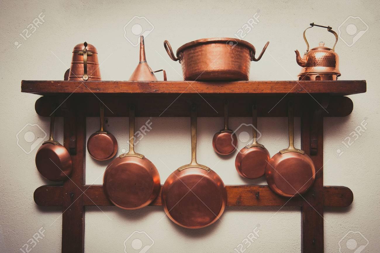 Appendi Pentole A Muro diversi tipi di pentole, pentole, caffè e imbuto in rame d'epoca appesi su  mensola in legno in cucina con parete rozza bianca