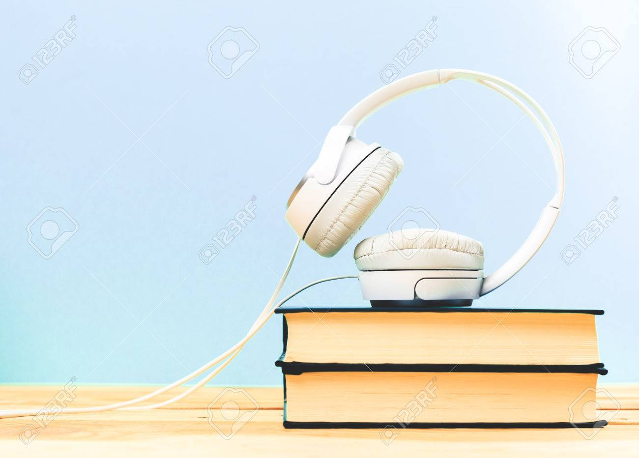 Concept of audiobook. Books on the table with headphones put on them - 76923463