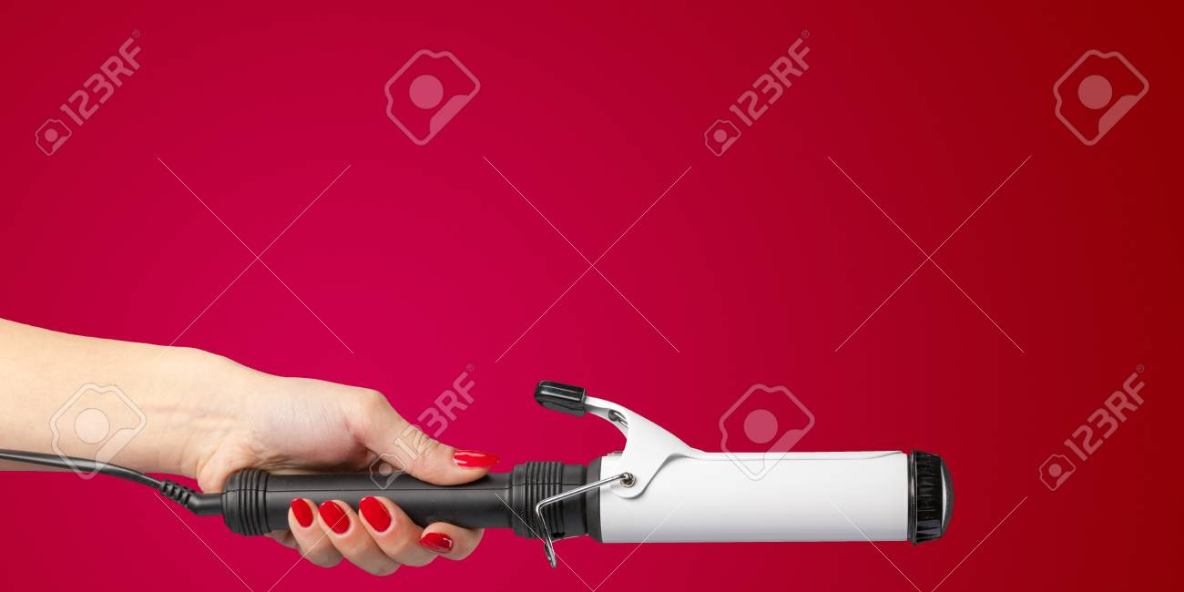 Woman Hand With A Hair Styler Isolated On Color Background Stock