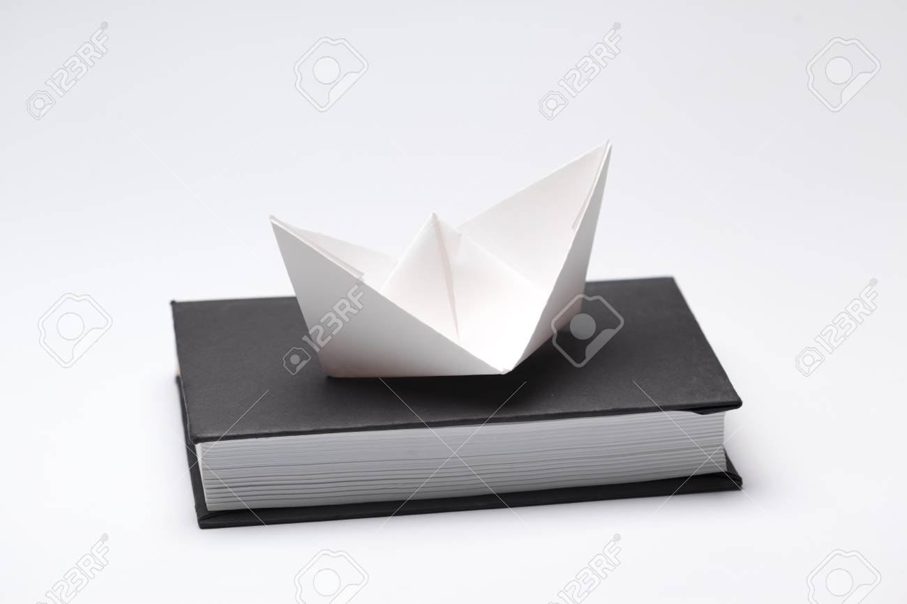 Origami Paper Boat On A Book Stock Photo Picture And Royalty Free