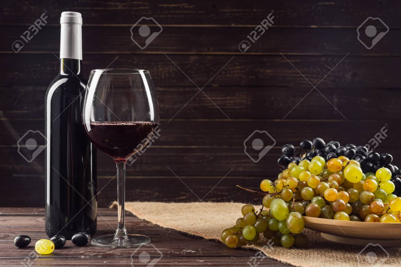 Wine bottle and grape on wooden table - 111527211