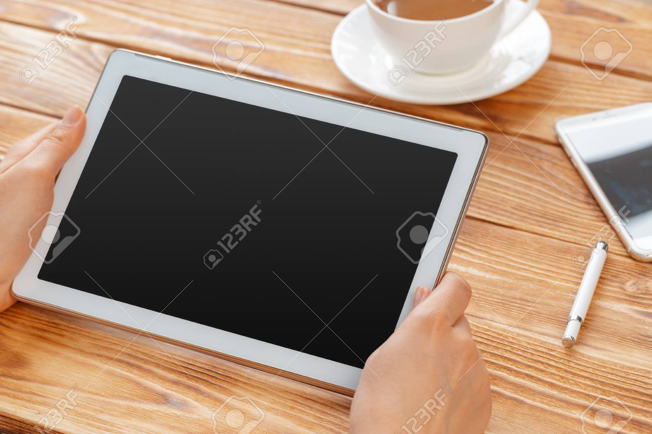 Close-up of young female hands holding digital tablet and drinking morning macchiato. - 111868048