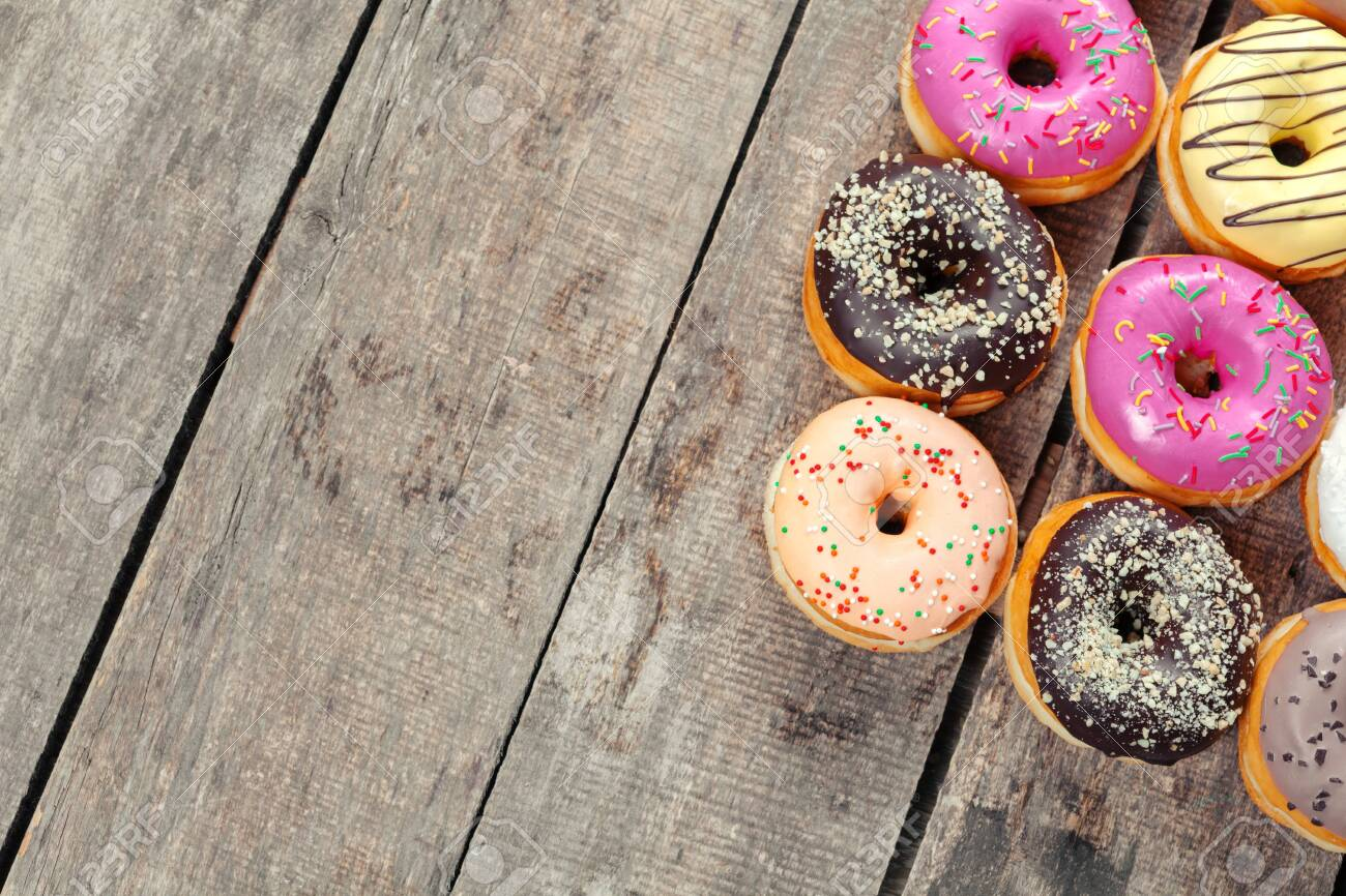 Glazed donuts on wooden background. Creative photo. - 142451864