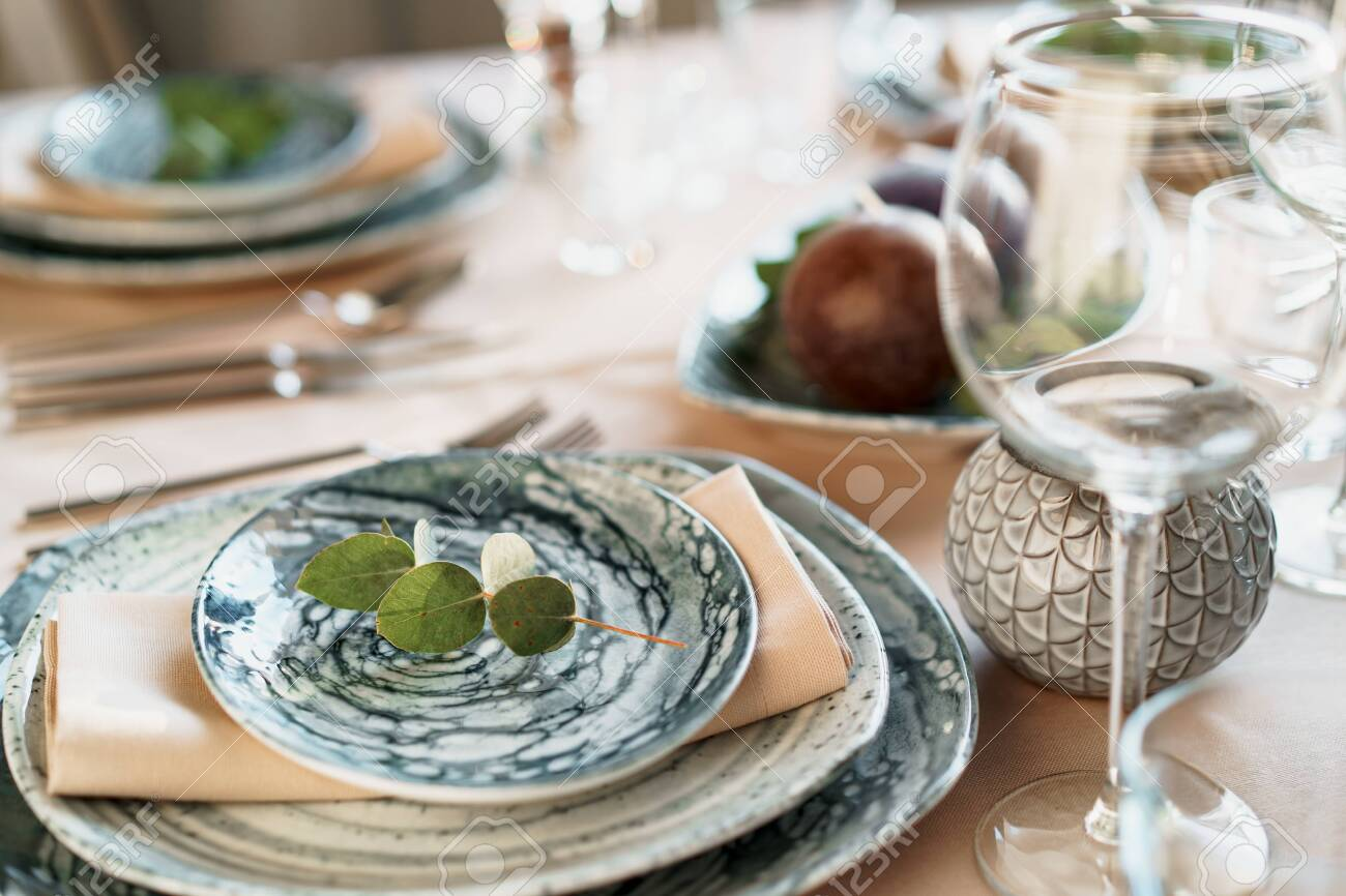 Beautiful elegant table setting with green stylish dishware and silver cutlery - 149664115