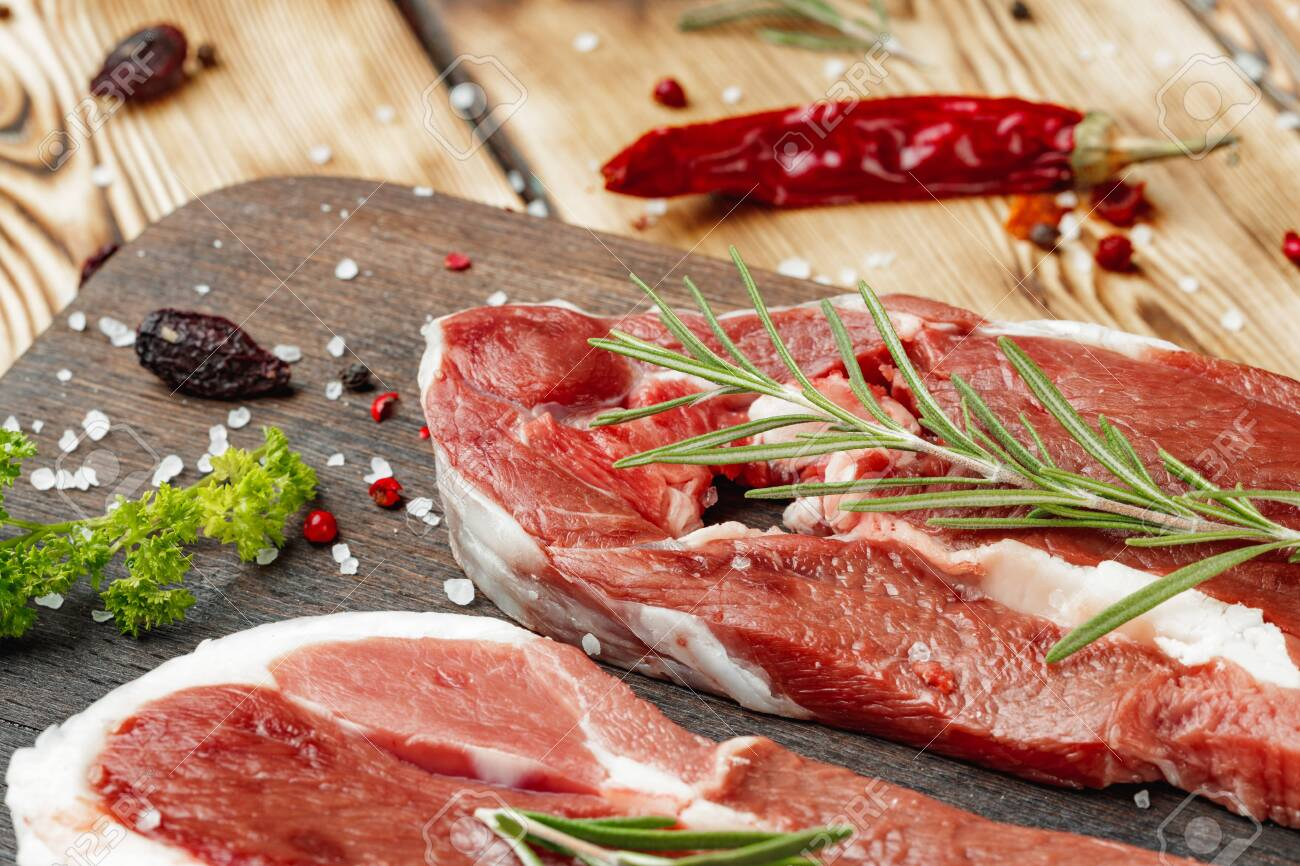 Raw meat steaks with herbs on wooden board - 149656494
