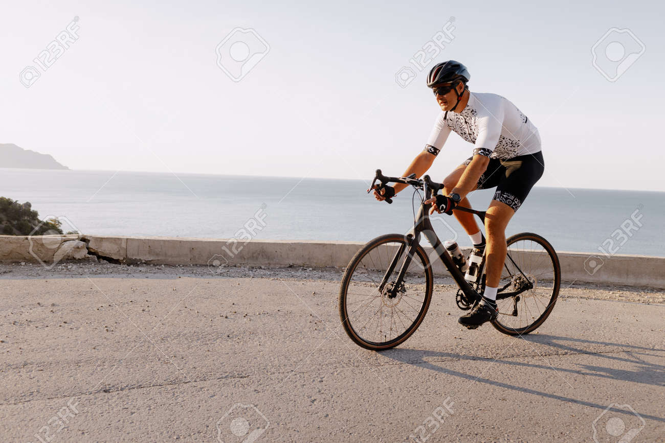 Professional road bicycle racer in action on mountain road - 155779653