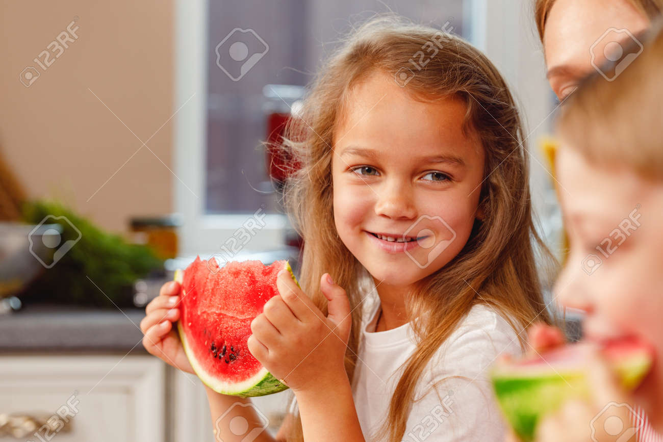 Smiling little girl eating a slice of watermelon in kitchen - 165810647
