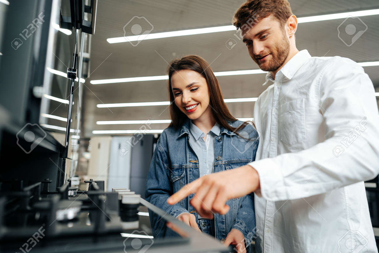 Young couple choosing new gas stove in home appliances store - 167838377