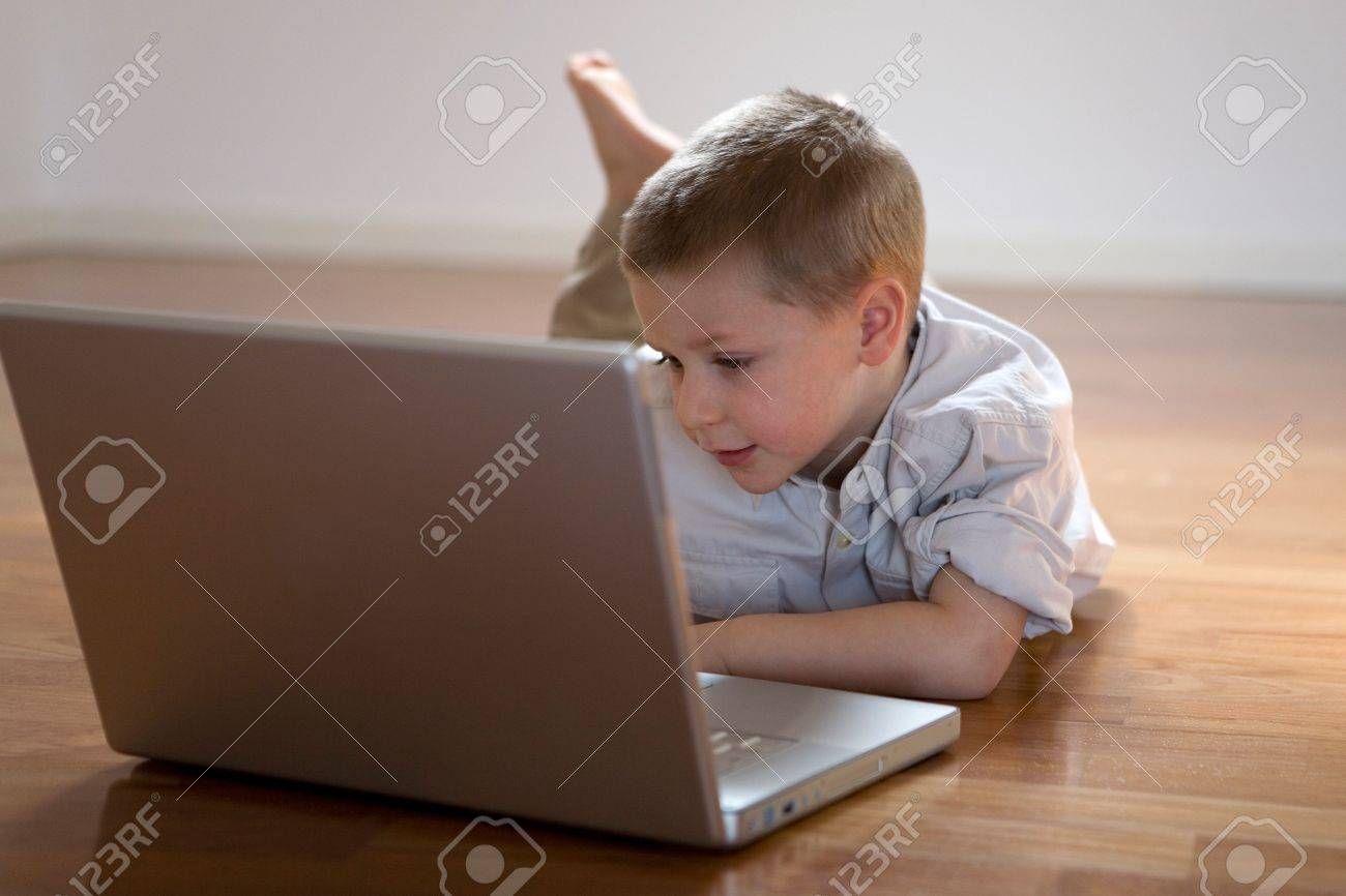 Happy child lying down on the floor using a computer Stock Photo - 918291