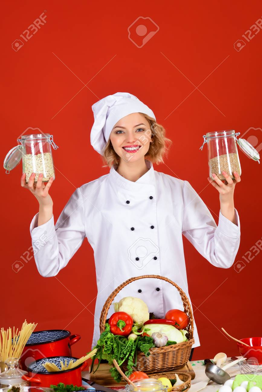 professional cook in white suit holding jars with cereal food