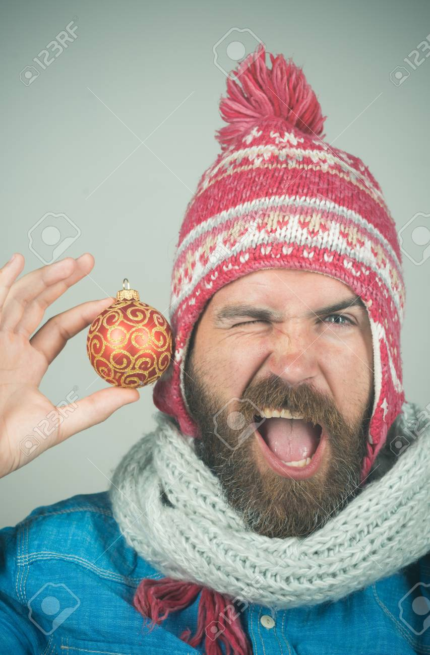 80002baaf72 Funny bearded guy in winter hat and white scarf holds New Year s toy.  Hipster with long beard