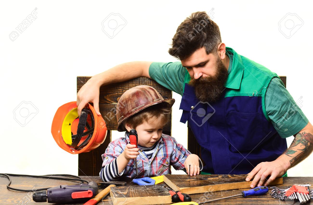 Father teaches son repair case. Son and father repairing together. Bearded man with little assistante. Boy works with screwdriver. Repair and engineering education. Dad teaches little son to use tools - 106265755