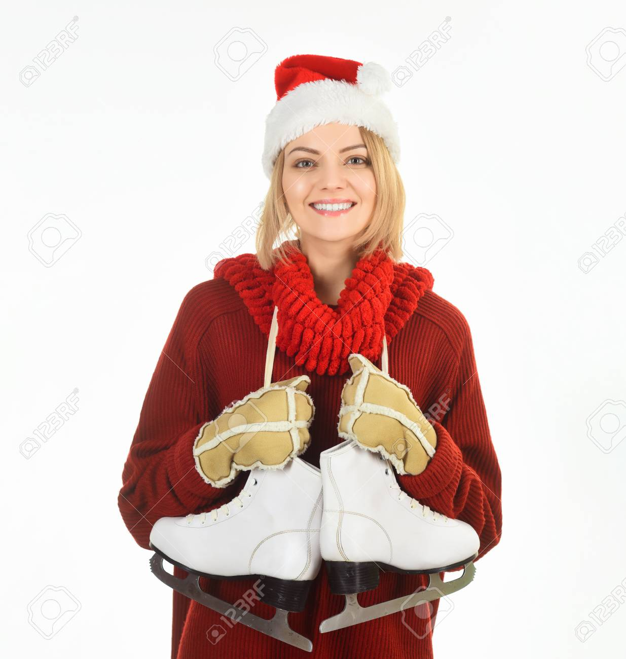 f676828e189 Girl in winter clothes with ice skates. Winter sport activity. Woman in Santa  hat