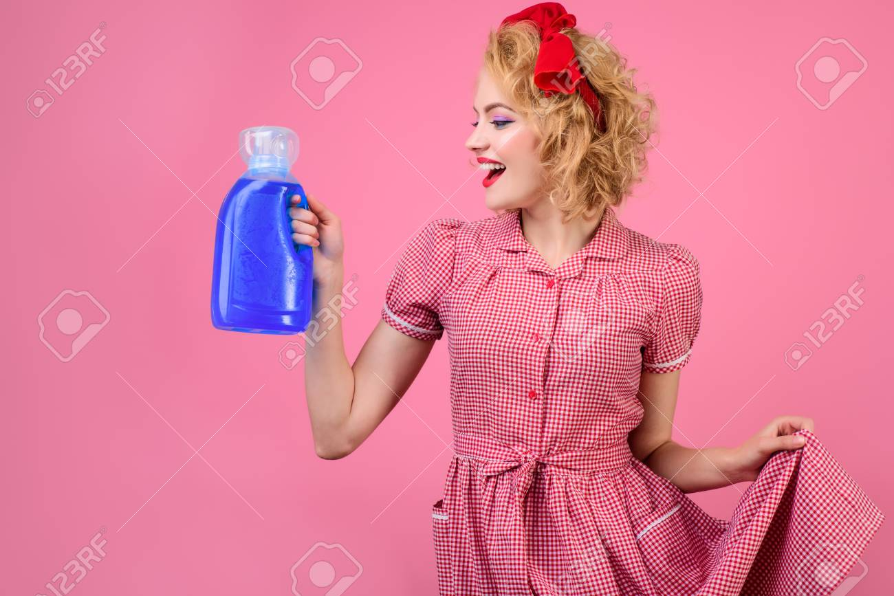 Portrait of pin up woman with cleaning products. Woman with bright makeup holds sponge and detergent. Retro style. Pin up clothes.