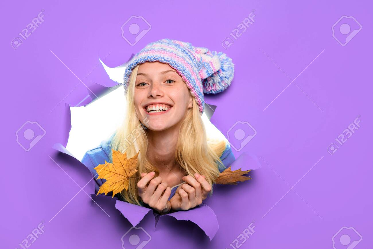 Happy girl in hat with maple leaves. Happy girl holds leaf. Autumn sales. Autumnal mood. Yellow maple leaf. Discount. Sales. Smiling woman with autumn leaves looking through paper hole. Copy space. - 127955709