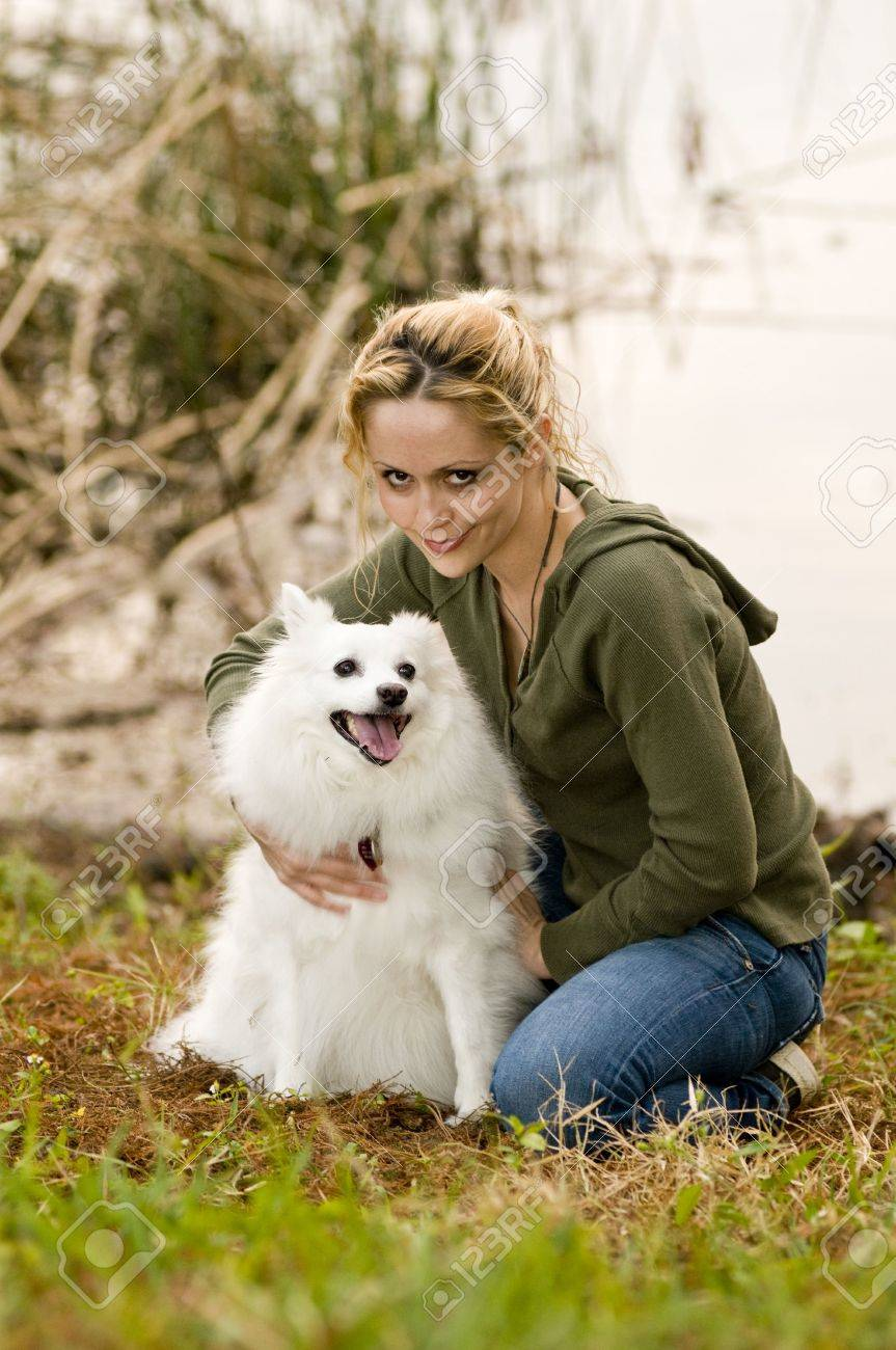 Young woman holding an American Eskimo dog Stock Photo - 6342153