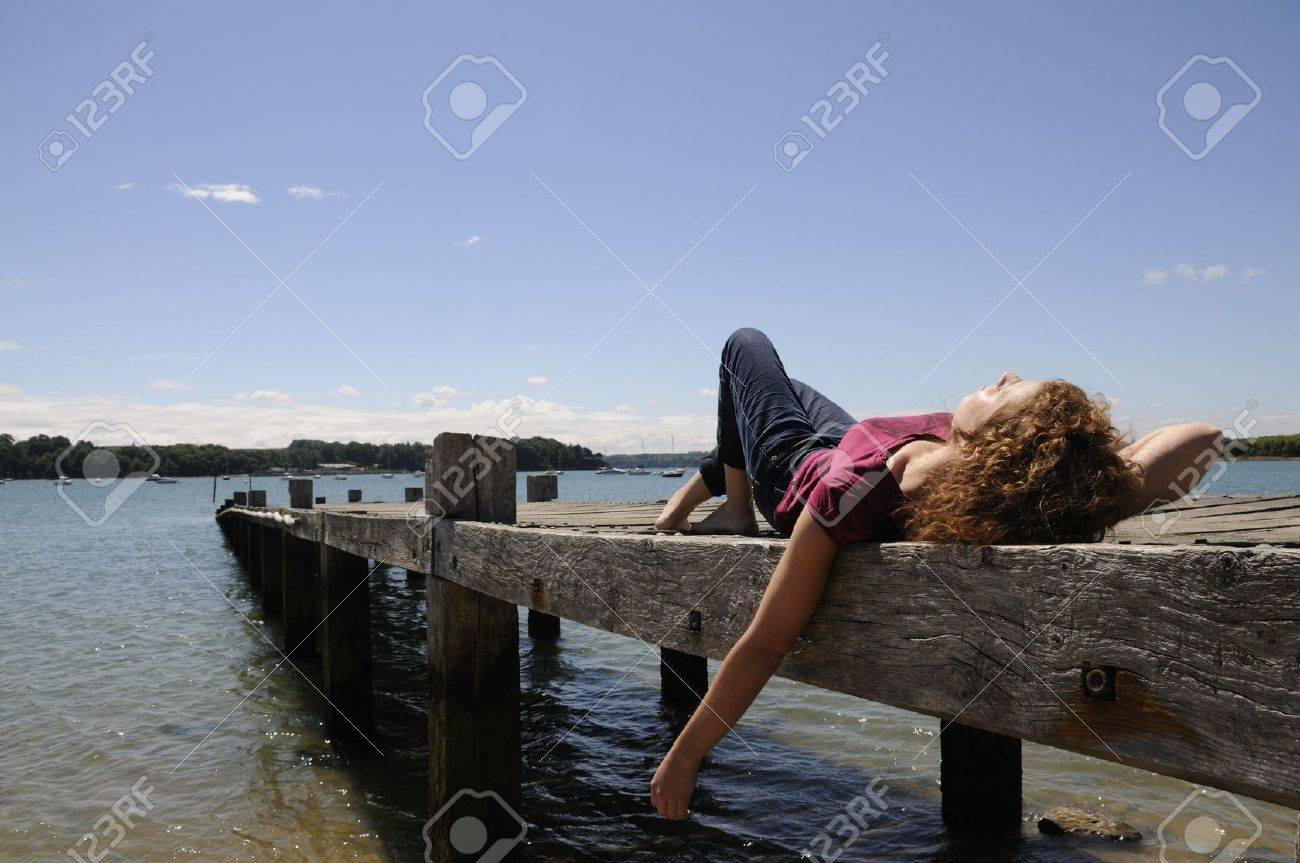 Pretty girl lying and relaxing on landing stage in Brittany, France on a sunny day. Stock Photo - 7657783