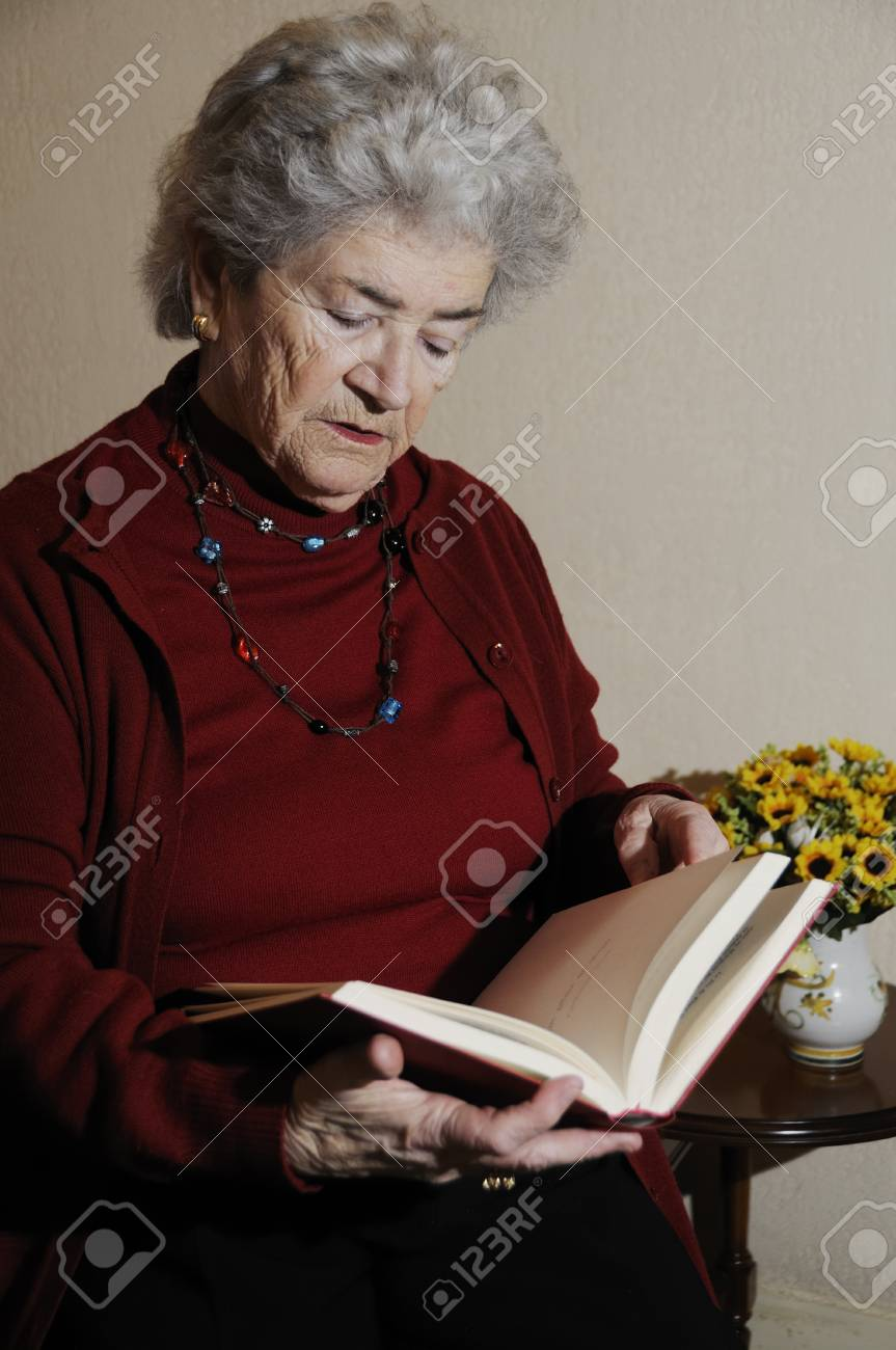 Old senior woman sitting on chair reading book Stock Photo - 8316658