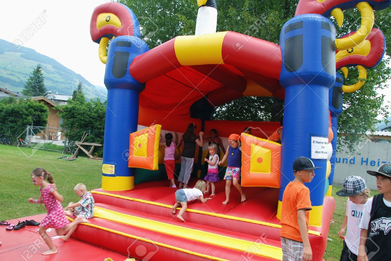 MITTERSILL, AUSTRIA - JUL 4: Children playing in inflatable castle at the supporting programme of the Water fun Event Erdinger Sautrogrennen on July 4, 2010 at the Zierteich in Mittersill, Austria Stock Photo - 8699075