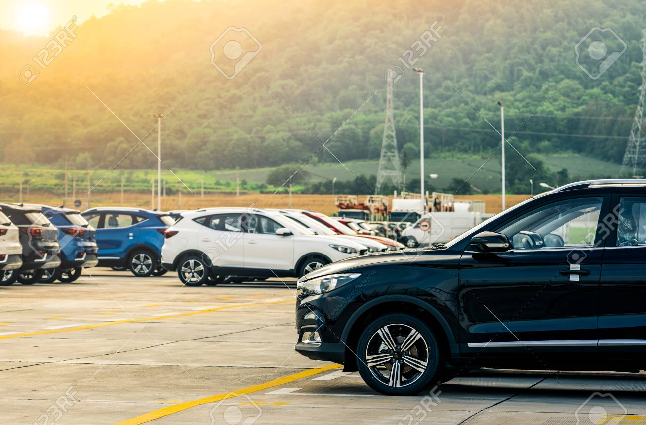 Black, white and blue new car parked on concrete parking area at factory near the mountain. Car dealership concept. Car stock for sale. Car factory parking lot. Automotive Industry concept. - 100920782