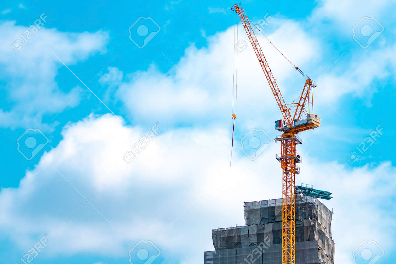 Construction site with crane and building. Real estate industry. Crane use reel lift up equipment in construction site. Building made of steel and concrete. Crane work against blue sky and white cloud - 121910952
