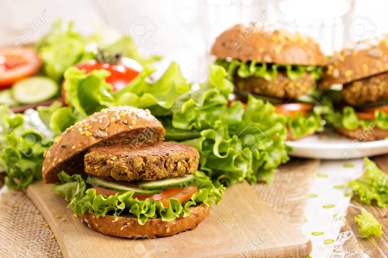 Vegan burgers with lentils and pistashios stacked on a cutting board - 42029074