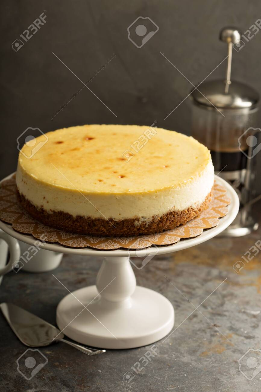 Homemade New York cheesecake on a cake stand decorated with fresh berries - 122038224