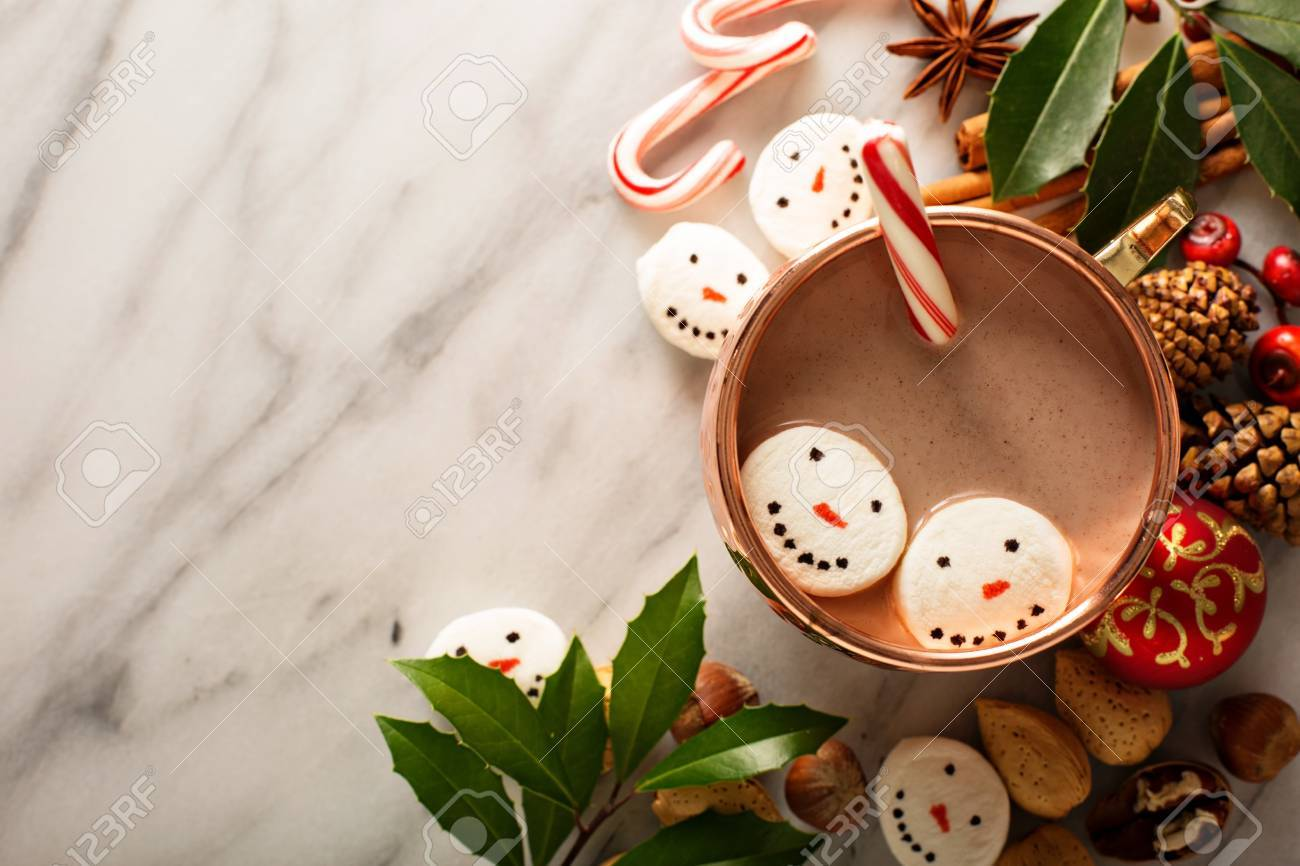 Hot cocoa with marshmallow snowmen and candy cane - 66844321