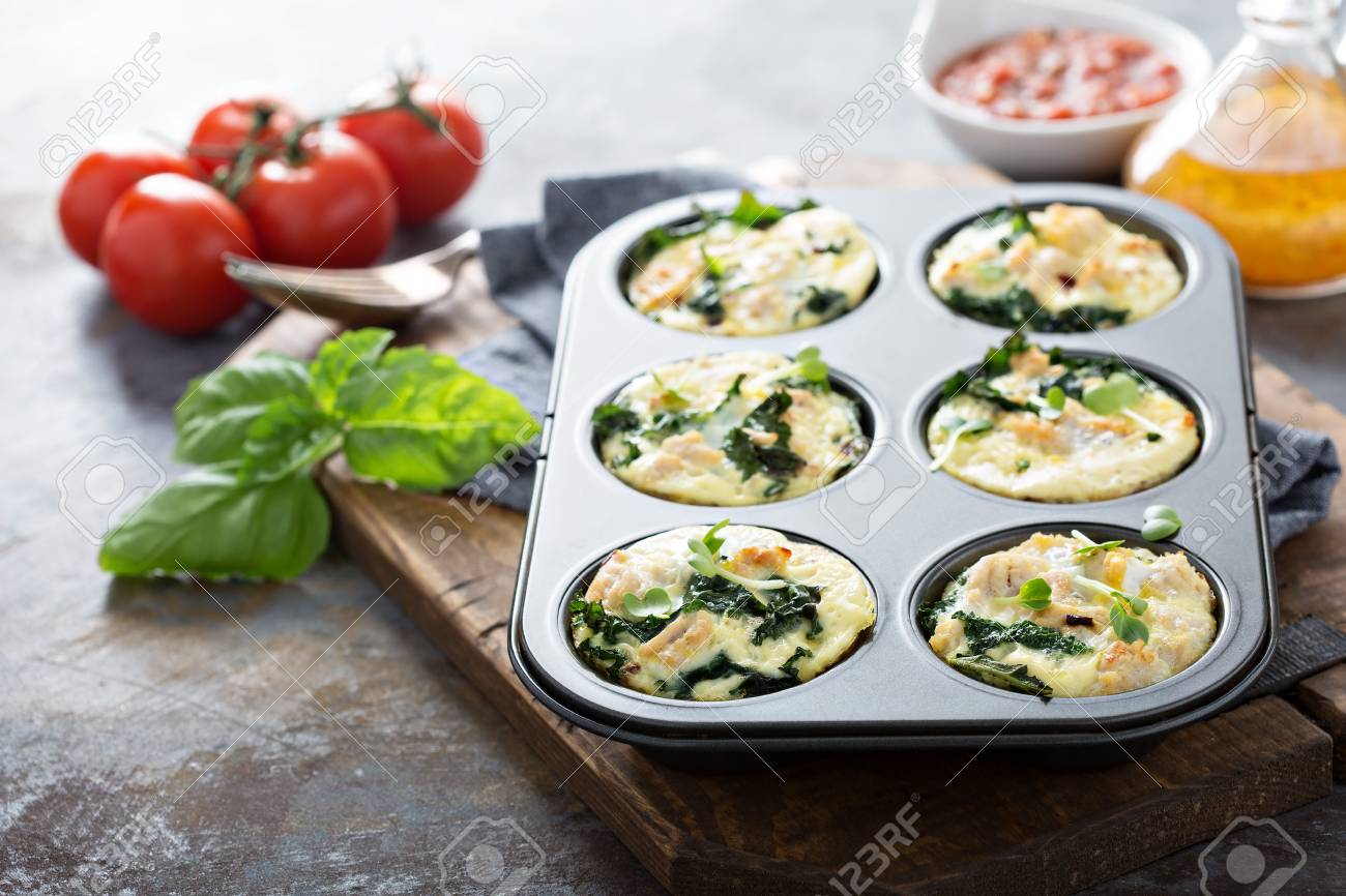 High protein egg muffins with kale and ground turkey in a muffin tin - 94418088