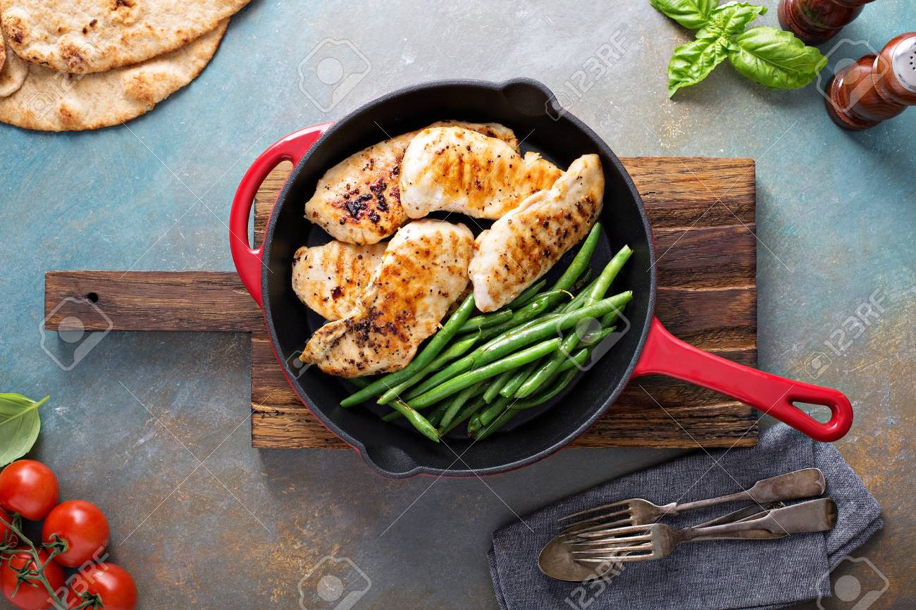 Grilled chicken with green beans in a cast iron skillet - 94417798