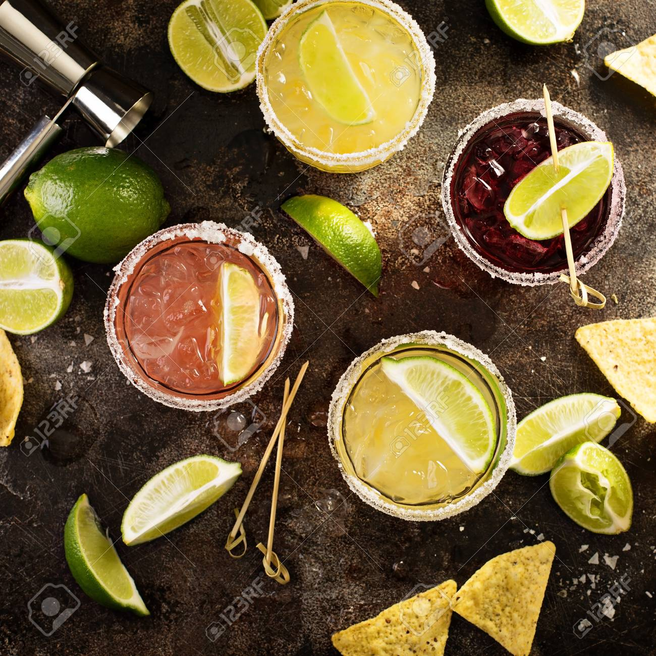 Variety of margarita cocktails with salted rim and lime on dark background overhead shot - 94474231
