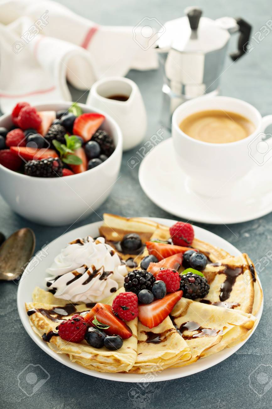 Thin crepes with whipped cream and berries - 96534674