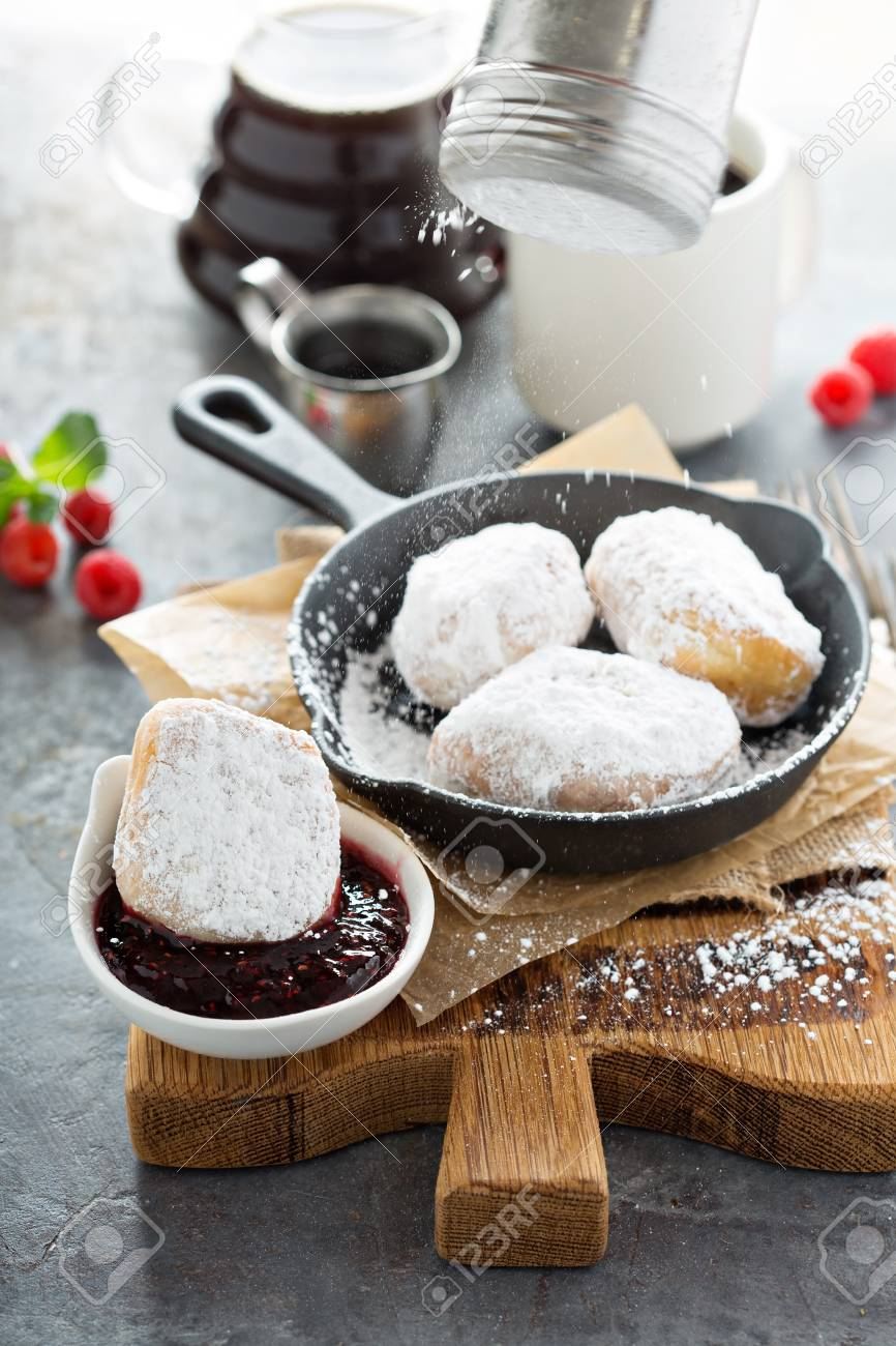 Beignets with powdered sugar pouring over and raspberry jam