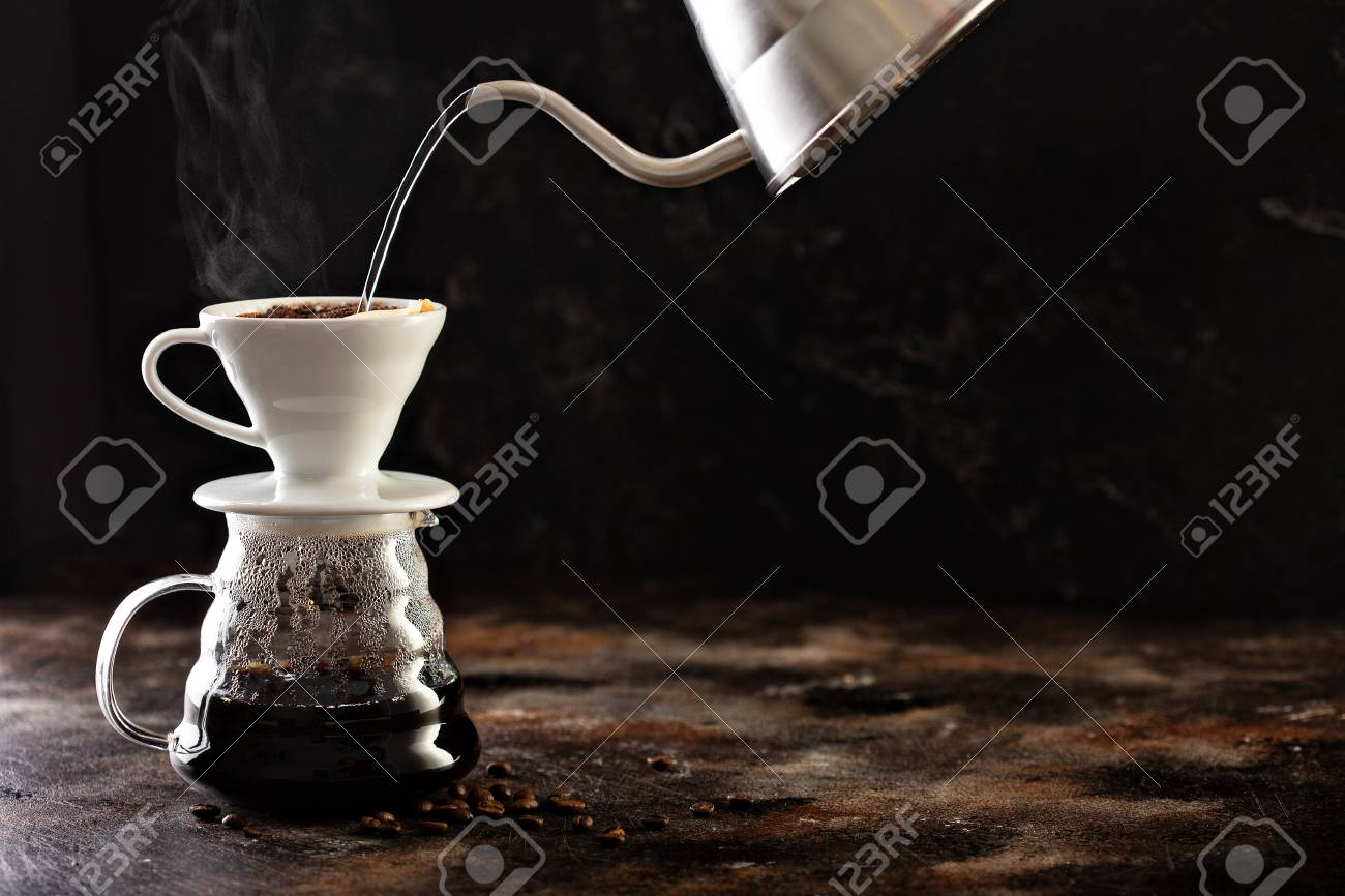 Making pour over coffee with hot water being poured from a kettle - 114550869