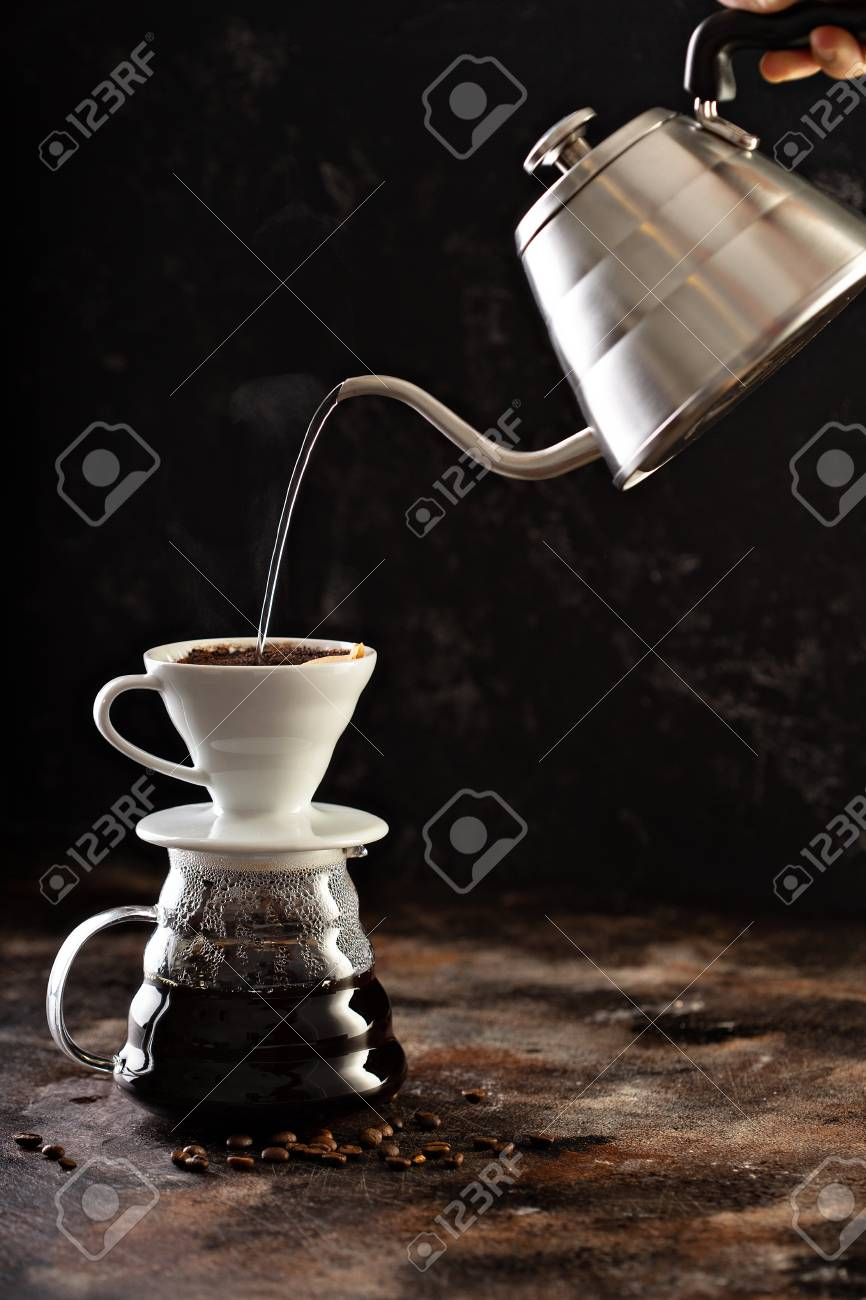 Making pour over coffee with hot water being poured from a kettle - 114550870
